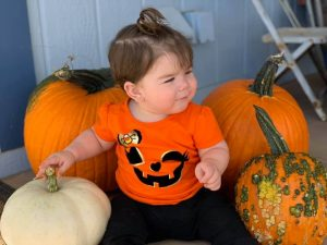 My granddaughter with the pumpkins. The zombie pumpkin is on the right!